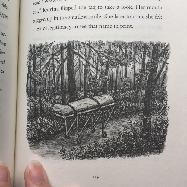 A gurney with a corpse inside a body bag waits on a path in a forest.